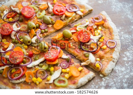 Vegetarian Pizza Slice - Vegetarian Pizza on a wooden table with white flour around it. Healthy replacement for a fast/ junk food version of pizza. High angle view. - stock photo