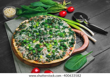 Vegetarian pizza with spinach leaves, mozzarella cheese, green onion, cherry tomatoes, knife on a black wooden background - stock photo