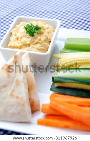 Vegetarian platter of raw carrots, corn, cucumber and celery sticks with chickpea dip and naan bread - stock photo