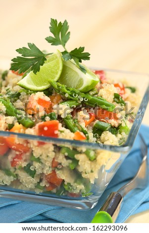 Vegetarian quinoa dish with green asparagus and red bell pepper, garnished with lime wedges and parsley leaf, served in glass bowl (Selective Focus, Focus on the asparagus head on the dish)     - stock photo