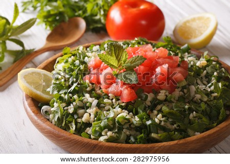 Vegetarian salad Tabbouleh close up in a wooden bowl and ingredients. horizontal