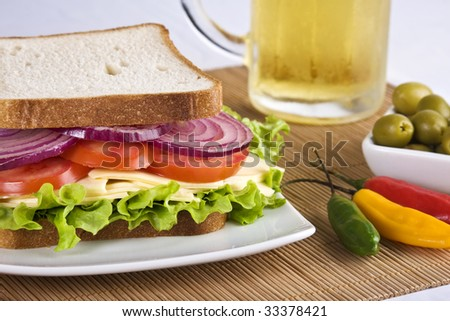 Vegetarian sandwich with cheese, tomato, lettuce and onion. A glass of cold beer and olives can be seen on the background. - stock photo