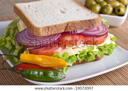 Vegetarian sandwich with cheese, tomato, onion and lettuce in white bread. - stock photo