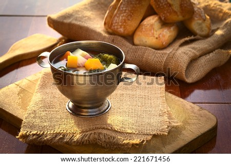 Vegetarian soup made of broccoli, squash, onion, carrot, potato and tomato served in a metal bowl, photographed with natural light (Selective Focus, Focus onto the first half of the soup) - stock photo