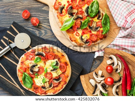 Vegetarian sourdough pizza with tomatoes, mozzarella and mushrooms, decorated with basil leafs, view from above