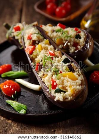 Vegetarian stuffed aubergine menu on a rustic wooden background - stock photo