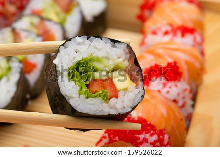 Vegetarian sushi roll in chopsticks on wooden dish - stock photo