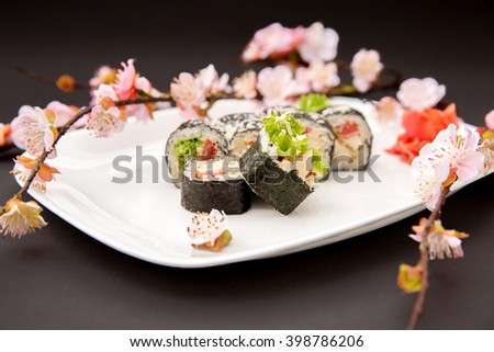 Vegetarian Sushi Roll with a bunch of blooming sakura - stock photo