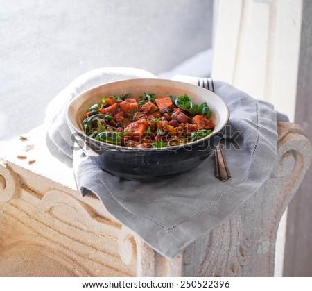 Vegetarian tasty spicy sweet potato quinoa chili in a wooden bowl - stock photo