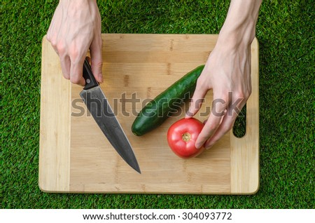 Vegetarians and cooking on the nature of the theme: human hand holding cucumber, tomato on a cutting board and a background of green grass top view - stock photo