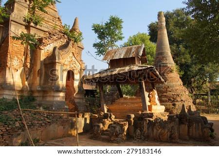 Vegetation reclaims ancient  Buddhist stupas at In Dein on  Inle Lake,  Myanmar (Burma) - stock photo