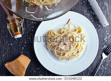Vegeterian italian pasta: spaghetti with garlic oil, red chili and parmesan in white plate on wood table background. Bottle of olive oil and big bowl with pasta near it - stock photo