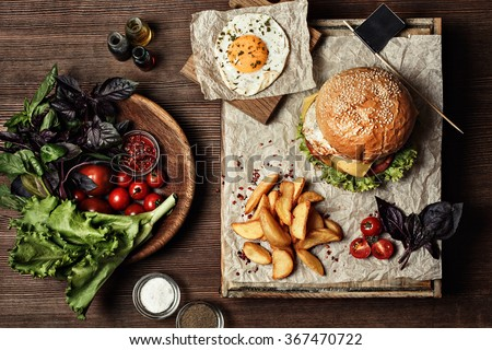 Veggie burger with salad, tomato and fries. Wooden background - stock photo