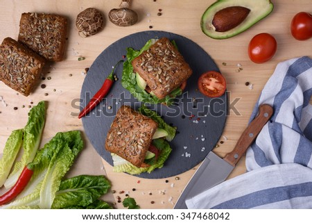 Veggie burger with shiitake, falafel and avocado, on wooden background, top view. - stock photo