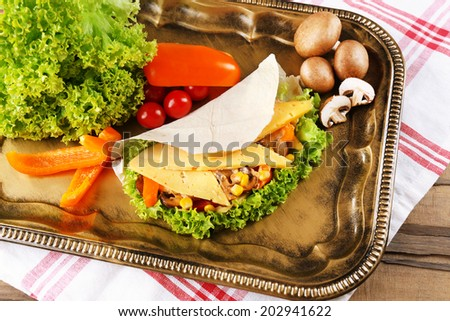 Veggie wrap filled with chicken and fresh vegetables on tray, close up