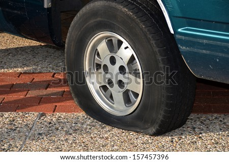 vehicle on city street with flat tire - stock photo
