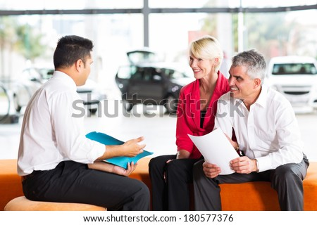 vehicle salesman explaining contract to senior couple before buying a car - stock photo