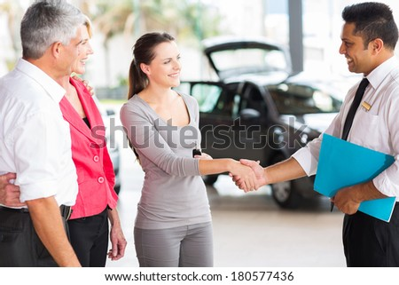 vehicle salesman handshaking with young adult customer after the sale - stock photo