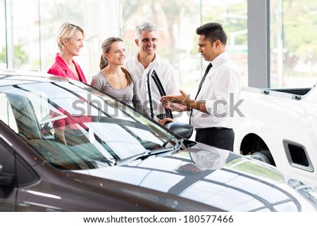 vehicle salesman showing new car to a family - stock photo