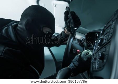 Vehicle Thief Concept Photo. Caucasian Car Thief in Black Mask. - stock photo