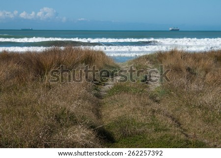 vehicle track through sand dunes at New Zealand surf beach with cargo ship on the horizon - stock photo