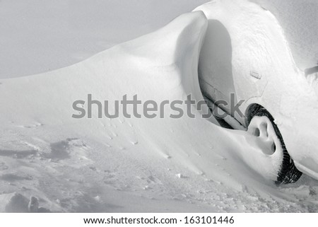 vehicles covered with snow in the winter blizzard in the parking lot - stock photo