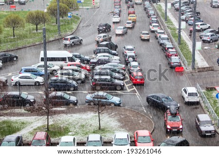 Vehicles parking on street and strong rain with snow - stock photo