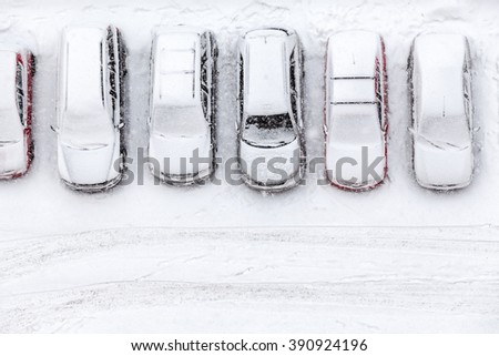 Vehicles standing at winter parking lot covering with snow, top view, copyspace