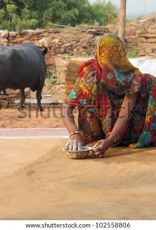 veiled woman sitting on the ground while painting an ornament in Karauli, India