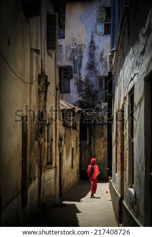 Veiled woman walking through a narrow street at Zanzibar - stock photo