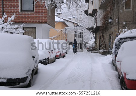 VELIKO TARNOVO, BULGARIA - JANUARY 6, 2017: Clearing snow from the car roof in General Gurko street on the winter day