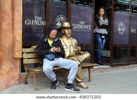 VELIKO TARNOVO, BULGARIA - MARCH 19, 2016: An unidentified Caucasian man and a girl next to the golden sitting statue of a gentleman - stock photo