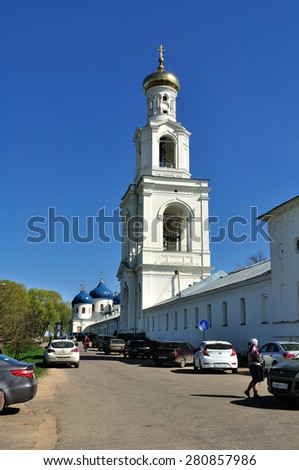 VELIKY NOVGOROD, RUSSIA - MAY 10. 2015.  The bell tower and Church of Exaltation of the Cross in Russian orthodox Yuriev Monastery, and parishioners walking along - stock photo