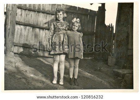 VELKY LOM, CZECHOSLOVAKIA, CIRCA 1950 - Two young girlfriends before the wooden gate (fence) - Circa 1950