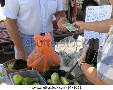 Vendor at farmers market receives cash to add to the wad already in pocket. - stock photo