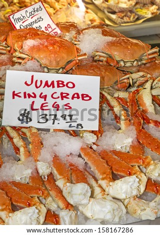 Vendor display selling fresh cooked jumbo king crab legs on ice  with price indicated. - stock photo