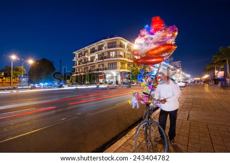 Vendor on bicycle selling bright balloons at evening asian city. Scene of night life at most popular tourist street near Royal Palace in capital city Phnom Penh, Cambodia - stock photo