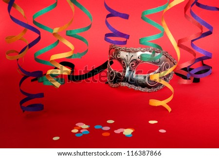 Venetian carnival mask and steamers on red - stock photo
