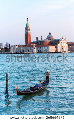 Venetian gondolier punting gondola through big canal waters of Venice Italy - stock photo