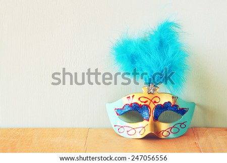 Venetian masquerade mask on wooden table. retro filtered image  - stock photo