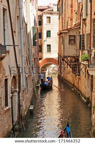 Venetian street with gondola on the narrow channel, Italy. - stock photo