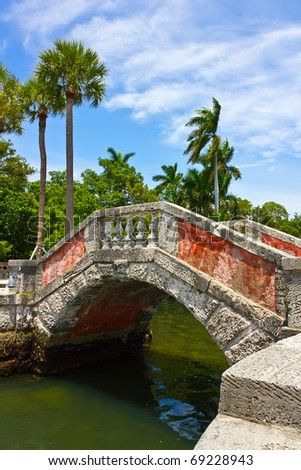 Venetian style bridge and palm trees at Vizcaya Museum & Garden in Miami, Florida - stock photo