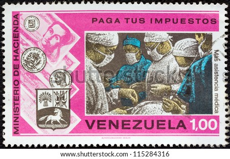 """VENEZUELA - CIRCA 1974: A stamp printed in Venezuela from the """"Pay Your Taxes Campaign"""" issue shows Surgical team in operating theatre, circa 1974. - stock photo"""