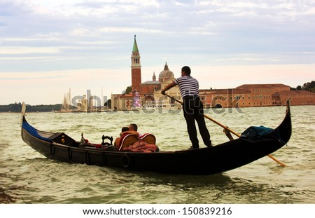 VENICE-AUGUST 18: Gondolier rides gondola at sunset on the Grand Canal of Venice on August 18, 2013. Gondola is one of the symbols of Venice and major mode of touristic transport in Venice, Italy.