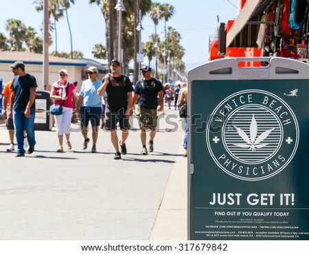 VENICE BEACH, USA - JUNE 4, 2014: A display on Venice Beach boardwalk showing advertising for Venice Beach Physicians with a big cannabis leaf in the middle. A group of people is walking by.  - stock photo