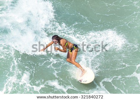 VENICE, CALIFORNIA, USA - AUGUST 22, 2015: Young woman surfing at Venice Beach on a beautiful sunny day.