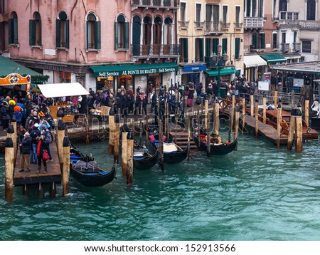 VENICE- FEB 19:A dock full of gondola near a specific street with unidentified people walking on February 19, 2012 in Venice.Gondola is a major mode of touristic transport in Venice.