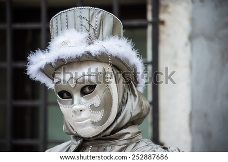 VENICE - FEB 13, 2015: An unidentified masked person in costume in St. Mark's Square during the Carnival of Venice on February 13, 2015. The 2015 carnival was held from February 7 Th to February 17Th - stock photo