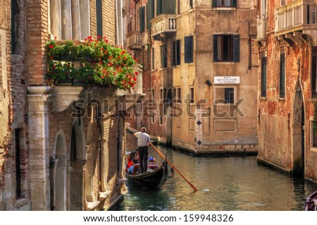 Venice, Italy. A romantic gondola floats on a narrow canal among old Venetian architecture