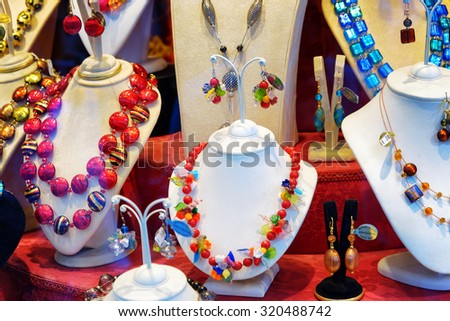 VENICE, ITALY - AUGUST 24, 2014: Colorful original jewelry from Murano Glass in shop window on the Rialto Bridge. Authentic beads, necklaces and earrings. Venice is a popular tourist destination. - stock photo